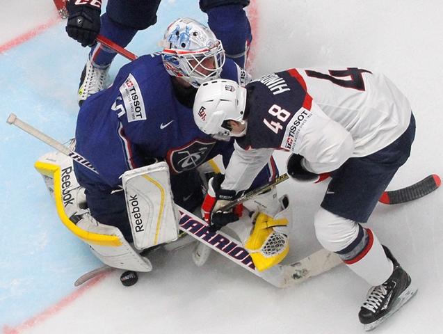 Na snímke hráč USA Vince Hinostroza (vpravo) sa snaží vydolovať puk spod brankára Francúzska Floriana Hardyho v zápase B-skupiny MS v hokeji USA - Francúzsko