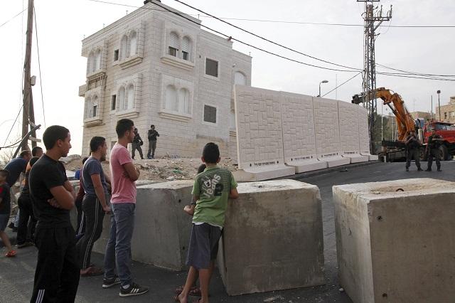Palestínčania sledujú výstavbu  betónového múru vo východnom Jeruzaleme, ktorý oddeľuje židovskú štvrť Armon Hanaciv od arabskej Džabal Mukaber