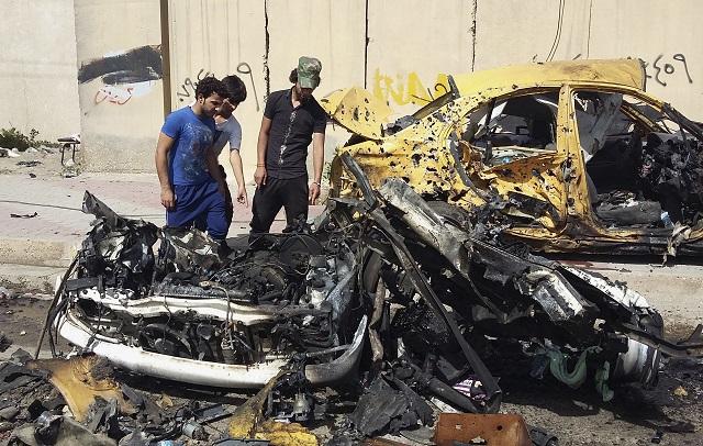 Irackí civilisti skúmajú miesto výbuchu bombovej nálože umiestnenej v aute na predmestí Bagdadu Sajdijá 2. mája 2016. Najmenej 22 šiitských pútnikov prišlo dnes o život pri výbuchu v aute nastraženej bomby na bagdadskom predmestí Sajdijá
