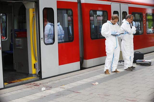 Nemeckí policajti vyšetrujú na mieste útoku nožom na železničnej stanici v Grafingu pri Mníchove 10. mája 2016. Dnešný útok muža ozbrojeného nožom na železničnej stanici v meste Grafing pri Mníchove si vyžiadal jedného mŕtveho a troch zranených