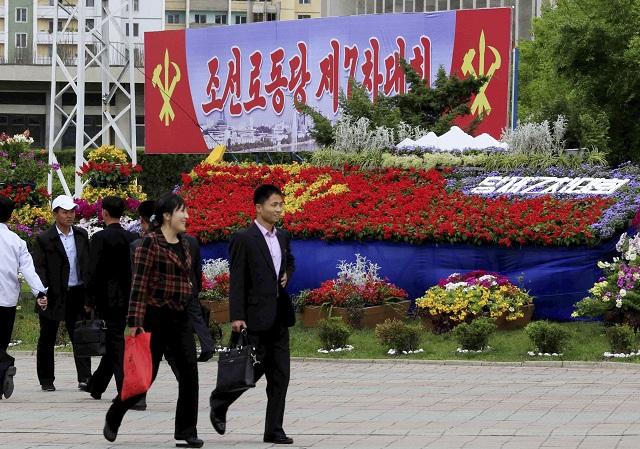 EBE 41 Pchjongjang - Na snímke ľudia kráčajú okolo kvetinovej výzdoby a bilbordov k 7. zjazdu vládnej Kórejskej strany práce (KSP) v severokórejskom Pchjongjangu 5. mája 2016