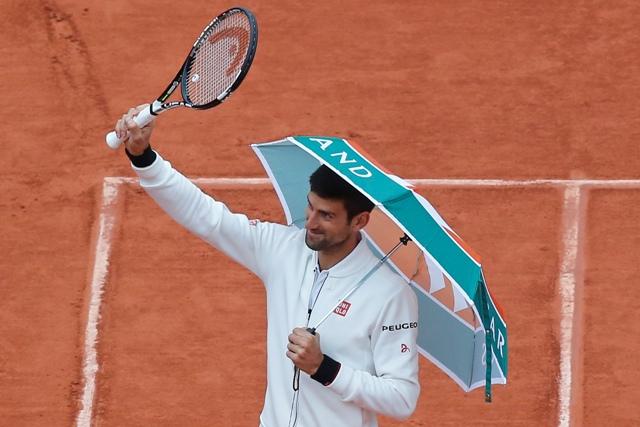 Na snímke srbský tenista Novak Djokovič opúšťa dorec pod dáždnikom po prerušení zápasu osemfinále so Španielom Robertom Bautistom Agutom kvôli dažďu na grandslamovom turnaji Roland Garros v Paríži