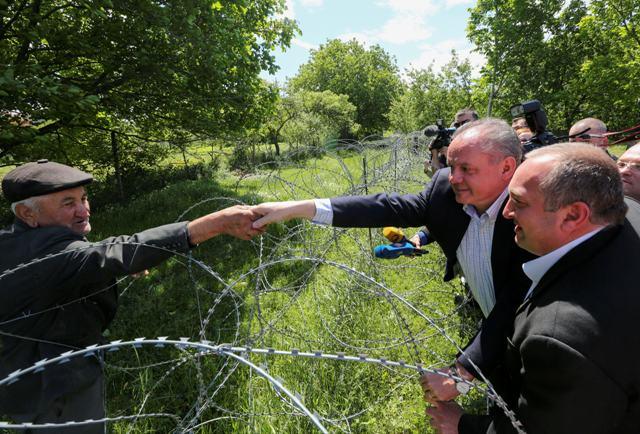 Slovenský prezident Andrej Kiska (druhý vpravo) si podáva cez ostnatý drôt ruku s etnickým Gruzíncom, ktorý žije  v gruzínskej odštiepeneckej republike Južné Osetsko, vpravo sa pozerá gruzínsky prezident Giorgi Margvelašvili neďaleko gruzínskej dediny Churvaleti 31. mája 2016