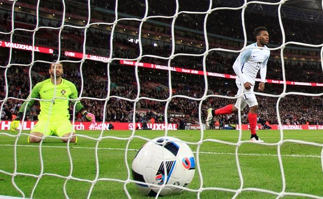 Portugalský brankár Rui Patricio kľačí na trávniku a pozará sa na loptu v bránke po hlavičke Chrisa Smallinga v prípravnom zápase Anglicko - Portugalsko