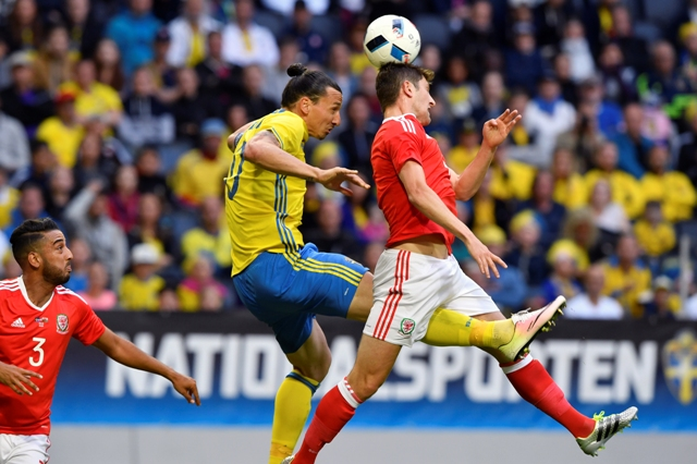Švédsky hráč Zlatan Ibrahimovič (vľavo) v súboji s Benom Daviesom z Walesu vo futbalovom prípravnom zápase Švédsko - Wales