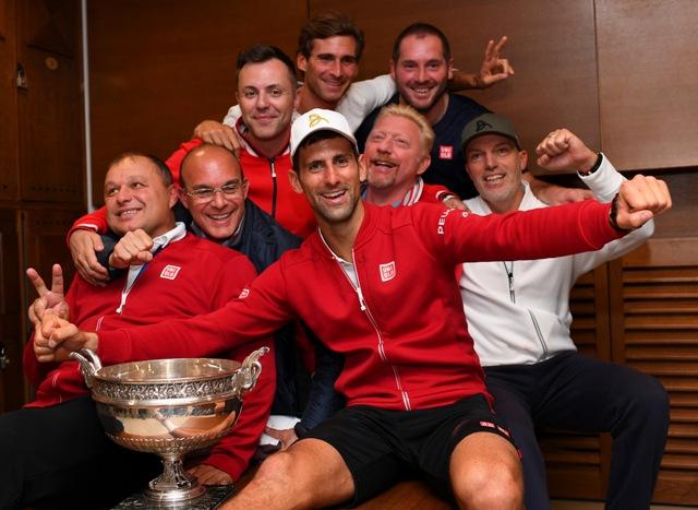 Srbský tenista Novak Djokovič pózuje v šatni so svojím tímom po víťazstve nad Britom Andym Murraym vo finále grandslamového tenisového turnaja Roland Garros v Paríži 5. júna 2016. Vľavo tréner Marián Vajda a druhý vpravo tréner Boris Becker