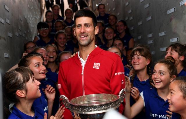 Srbský tenista Novak Djokovič sa raduje zberačkami loptičiek po jeho víťazstve nad Britom Andym Murraym vo finále grandslamového tenisového turnaja Roland Garros v Paríži