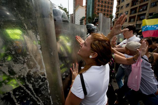 Snímka z protivládnej demonštrácie, kde protivládni demonštranti argumentujú s príslušníkmi bezpečnostných síl počas demonštrácie proti venezuelskému prezidentovi Nicolásovi Madurovi v Caracase 18. mája 2016