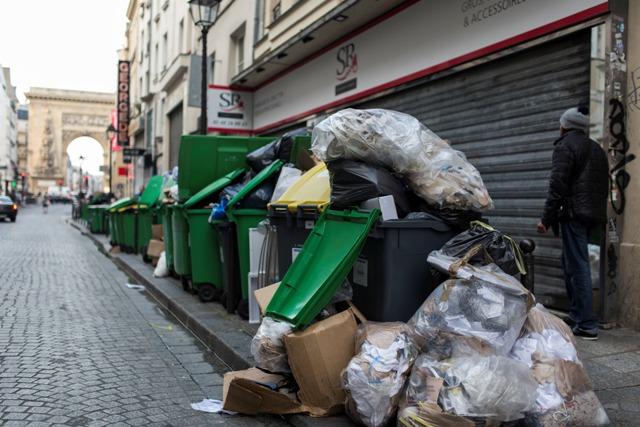 Ľudia kráčajú okolo kopiacich sa odpakov na ulici V Paríži počas štrajku smetiarov