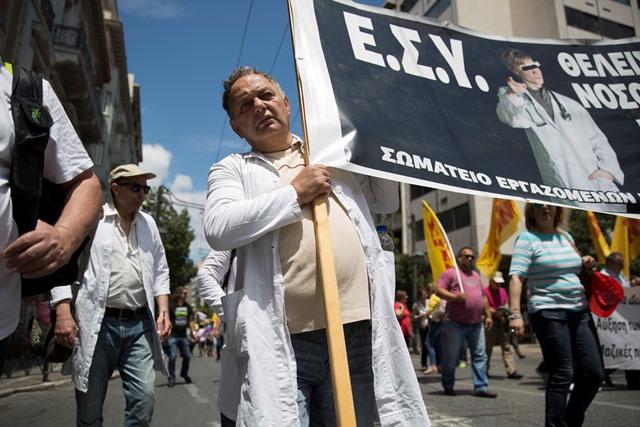 Na snímke štrajkujúci zamestnanci štátnych nemocníc skandujú počas protestného pochodu proti pripravovanej reforme v zdravotníctve v centrálnych Aténach