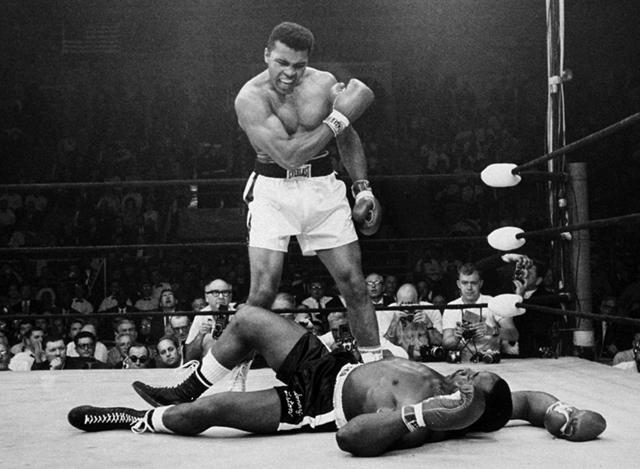 Na archívnej snímke z 25. mája 1965   niekoľkonásobný svetový boxerský šampión v ťažkej váhe Muhammad Ali  stojí nad zdolaným súperom Sonnym  Listonom  v zápase v Lewistone v americkom štáte Maine