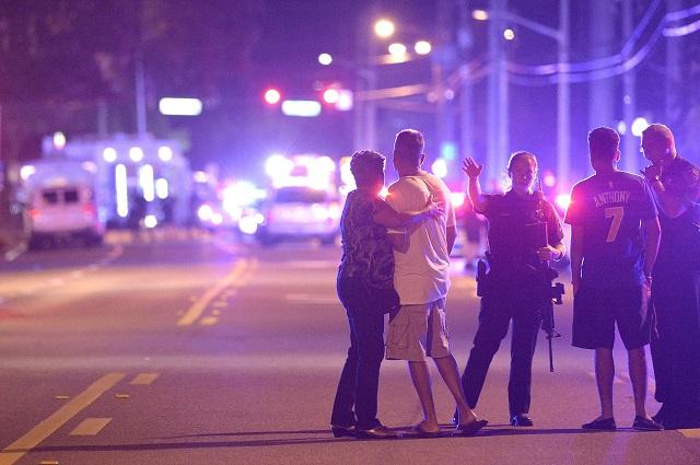 Policajti s rodinnými príslušníkmi  čakajú na ulici po streľbe v nočnom klube v Orlande