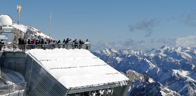 Skupina turistov fotografuje okolie z plošiny počas slnečného dňa na najvyššej nemeckej hore Zugspitze (2962 m) v Bavorských Alpách na hraniciach s Rakúskom