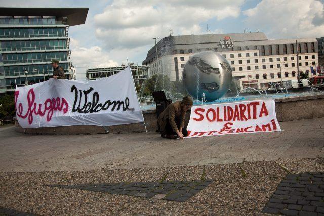 Na snímke muž s transparentmi, pričom na jednom je veľký nápis solidarita