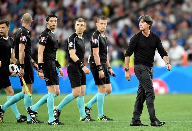 Tréner nemeckej futbalovej reprezentácie Joachim Löw (vpravo) odchádza z ihriska s rozhodcami po zápase semifinále ME vo futbale Nemecko - Francúzsko v Marseille