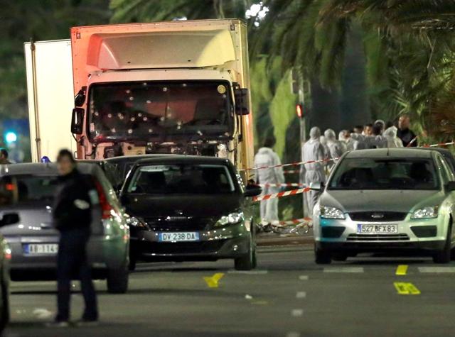 Forenzní technici stoja pri rozstrieľanej kabíne nákladného auta na mieste teroristického útoku na promenáde v Nice