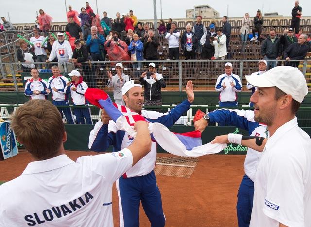 Na snímke slovenskí reprezentanti Andrej Martin (vľavo) a Igor Zelenay (vpravo) sa tešia so spoluhráčom Norbertom Gombošom po výhre 3:0 na sety v zápase štvorhry proti maďarskému páru Márton Fucsovics, Levente Gödry v 2. kole 1. skupiny euro-africkej zóny Davisovho pohára