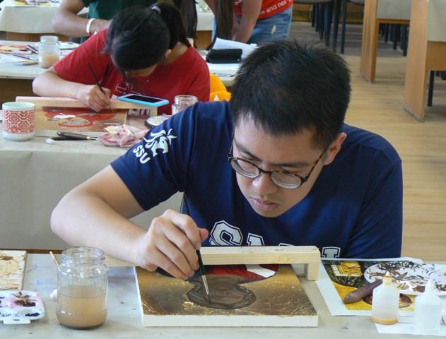 Na snímke v popredí Raphael Yeo zo Singapuru maľuje ikonu Krista
