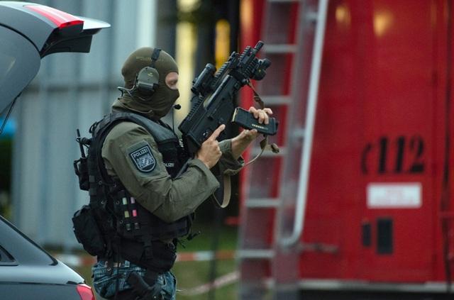 Ilustračné foto: Príslušník špeciálnej policajnej jednotky prehľadáva obytnú štvrť pri nákupnom centre Olympia v bavorskej metropole Mníchov, kde si streľba vyžiadala mŕtvych a zranených