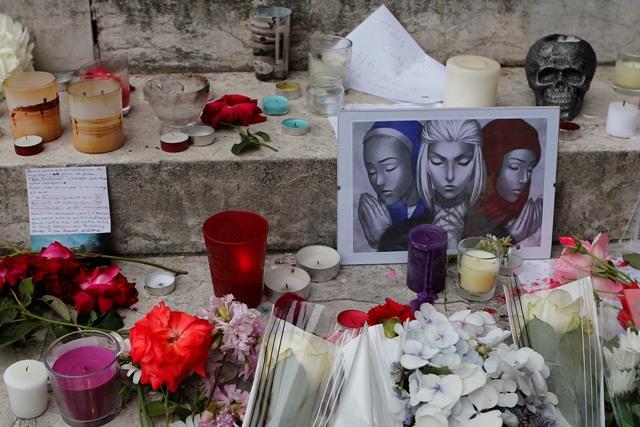 Sviečky, maľby a kvety položené pri pamätníku pred radnicou v Saint-Etienne-du-Rouvray 27. júla 2016 po útoku na kostol, pri ktorom zahynul kňaz