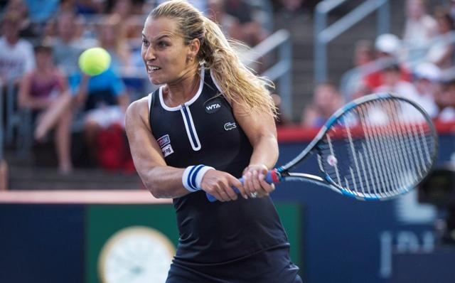 Slovenská tenistka Dominika Cibulková odvracia úder domácej Kanaďanky Eugenie Bouchardovej v zápase 2. kola ženskej dvojhry na tenisovom turnaji WTA v Montreale