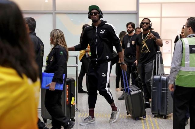 Jamajský olympijský šprintér Usain Bolt  (v strede) kráča po prílete na medzinárodné letisko v Rio de Janeiru 28. júla 2016 počas príchodu na nadchádzajúce olympijské hry
