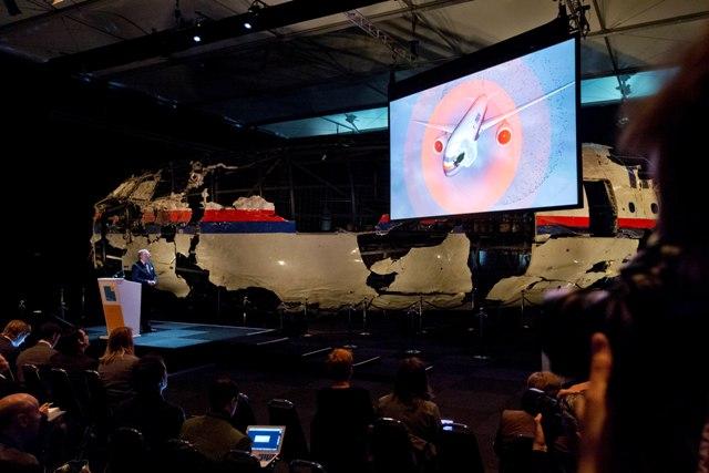 Videoprezentácia ukazuje  dopad rakety na lietadlo malajzijskej leteckej spoločnosti Malaysia Airline, let MH17, v pozadí je časť rekonštruovanej prednej časti trupu lietadla