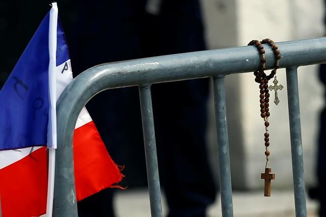 Francúzska zástava a ruženec položené pri pamätníku pred kostolom v Saint-Etienne-du-Rouvray 28. júla 2016, v ktorom po útoku islamistov zahynul kňaz