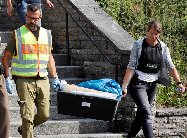 Príslušníci polície odnášajú z hotela v bavorskom Ansbachu osobné veci 27-ročného Sýrčana, ktorý odpálil v nedeľu večer nálož