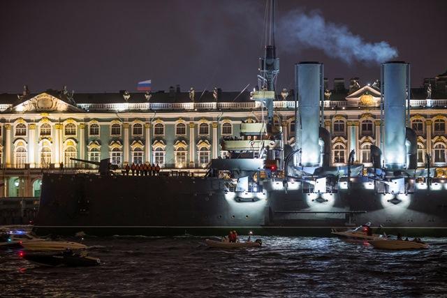 Na snímke člny ťahajú krížnik Aurora po rieke Neva okolo Zimného paláca v Petrohrade