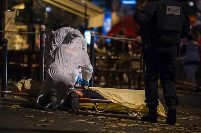 Na snímke forénzni experti prehľadávajú telo obete streľby v parížskom klube Bataclan
