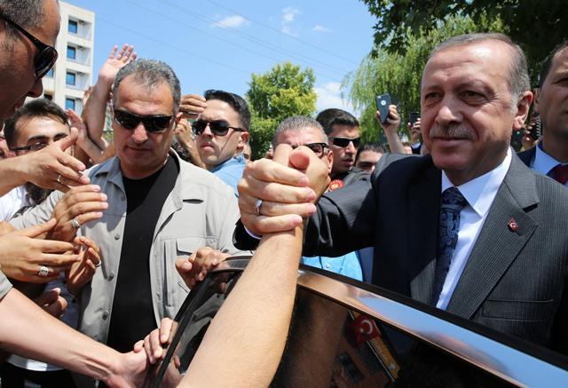 Na snímke turecký prezident Recep Tayyip  Erdogan (vpravo) si podáva ruky s ľuďmi