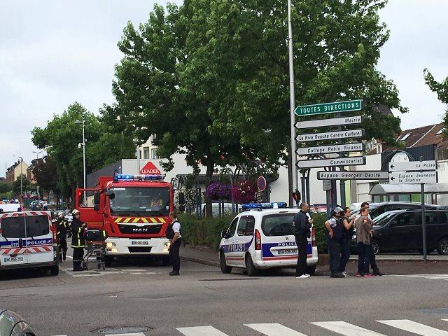 Na snímke polícia a záchranka pred kostolom, kde sa rukojemnícka dráma odohrala