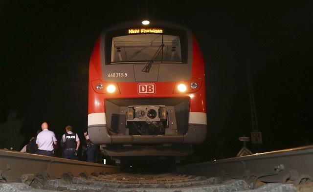 Policajní vyšetrovatelia stoja pri vlaku, v ktorom došlo k incidentu