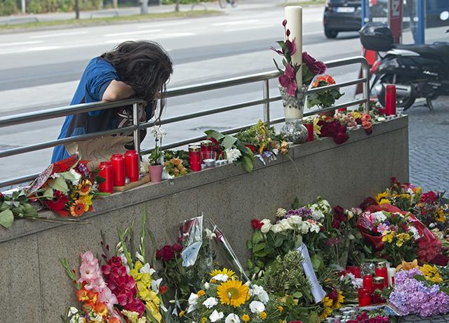 Na snímke žena smúti na mieste plnom kvetov a sviečok, kde v piatok zastrelil 18-ročný iránsky imigrant s nemeckým a iránskym občianstvom 10 ľudí vrátane seba v mníchovskom McDonalde a nákupnom centre v nedeľu 24. júla 2016.