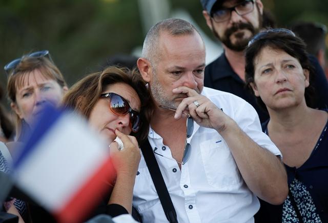 Na snímke ľudia smútia neďaleko miesta, na ktorom nákladné auto vrazilo do davu ľudí
