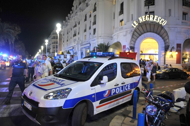 Na snímke ľudia stoja za policajným autom neďaleko miesta teroristického útoku