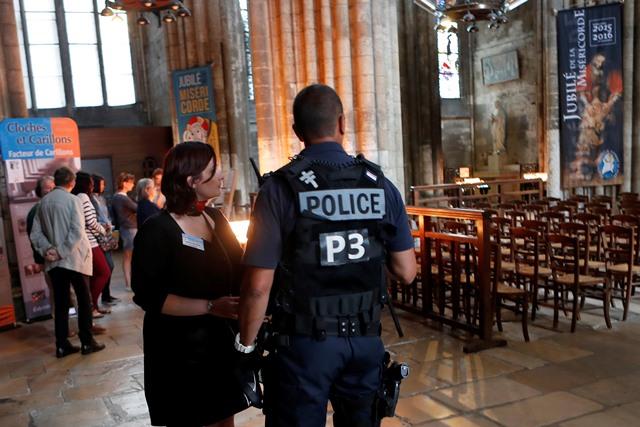 Na snímke policajt počas omše v katedrále Notre-Dame