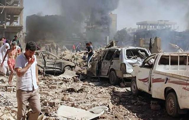 Na snímke miestni obyvatelia si prezerajú škody po dvoch bombových útokoch v prevažne kurdskom meste Kámišlí