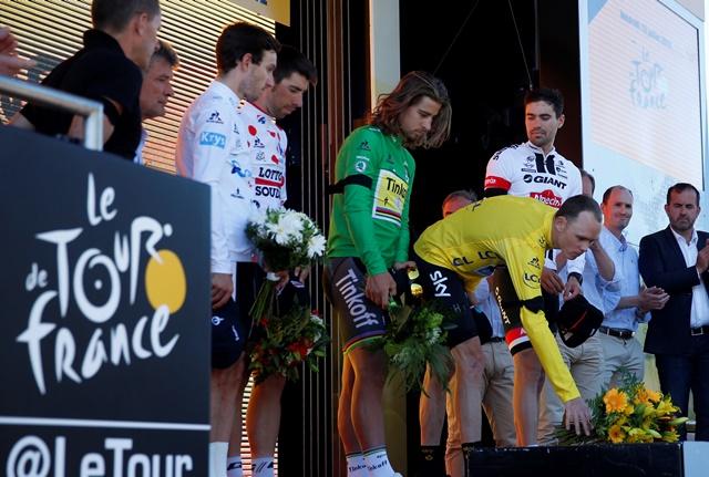 Na snímke Brit Adam Yates v tričku pre najlepšieho pretekára do 25 rokov,  belgický cyklista Thomas de Gendt v bodkovanom tričku pre najlepšieho vrchára, slovenský cyklista Peter Sagan zo stajne Tinkoff v zelenom drese pre lídra bodovacej súťaže, britský cyklista Chris Froome zo stajne Sky v žltom drese pre lídra priebežného poradia a víťaz 13. etapy holandský cyklista Tom Dumoulin kladú kvety po minúte ticha za obete teroristického útoku z francúzskeho Nice, na pódiu po 13. etape 103. ročníka prestížnych cyklistických pretekov Tour de France