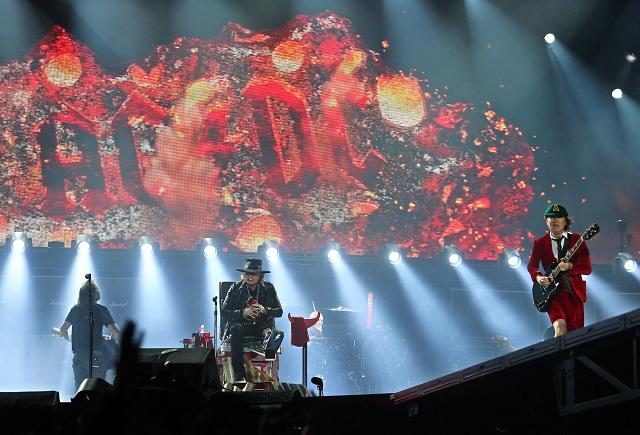 Na snímke vpravo gitarista skupiny AC/DC  Angus Young, vľavo gitarista Stevie Young a spevák skupiny Guns N' Roses Axl Rose