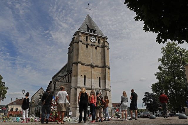 Ľudia sa zhromažďujú pri pamätníku pred kostolom v Saint-Etienne-du-Rouvray 28. júla 2016, v ktorom po útoku islamistov zahynul kňaz. Dvaja muži vyzbrojení nožmi vtrhli 26. júla do kostola v normandskom meste Saint-Étienne-du-Rouvray počas rannej omše, pričom zajali rukojemníkov a predtým, ako ich zlikvidovala polícia, podrezali hrdlo 84-ročnému kňazovi a ťažko zranili ďalšiu osobu. K zodpovednosti za útok sa prihlásila teroristická organizácia Islamský štát (IS)