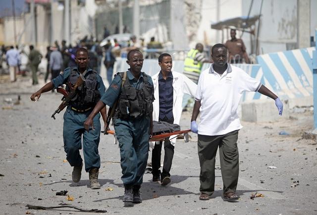 Somálski vojaci a strážnici odmínovacej agentúry OSN (UNMAS) odnášajú telo svojho kolegu po samovražednom útoku atentátnika, ktorý sa odpálil v aute naloženom výbušninami  pred kanceláriami UNMAS v somálskej metropole Mogadišo 26. júla 2016