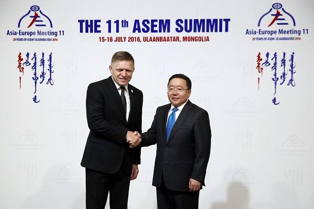 Na snímke vľavo predeseda vlády SR Robert Fico a vpravo mongolský prezident Cachjagín Elbegdordž počas príchodu na 11. európsko-ázijský samit ASEM v Ulanbátare v Mongolsku 15. júla 2016