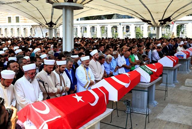 Na snímke smútiaci sa modlia vedľa truhiel s pozostatkami