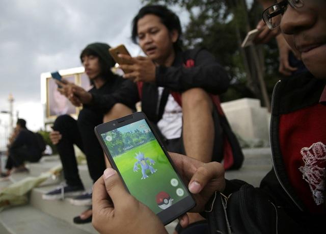 Muž hrá na smartfóne hru Pokémon Go