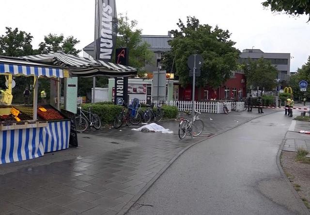 Na snímke z videozáznamu je telo prikryté plachtou po streľbe v nákupnom centre Olympia. Útok strelcov si vyžiadal mŕtvych a zranených