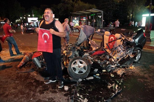 Na snímke muž pózuje s tureckou vlajkou pred autom, ktorý zničil vojenský tank 16. júla 2016 v Ankare