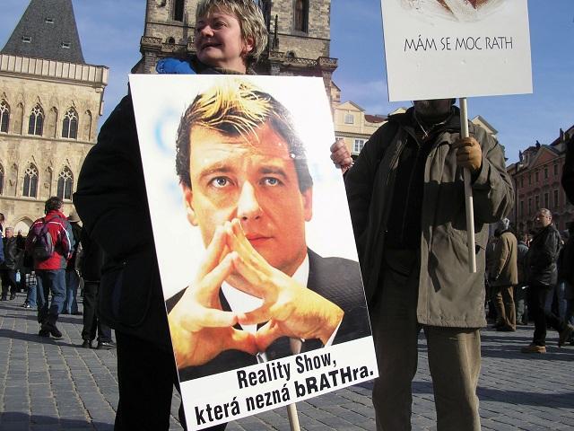 Český minister zdravotníctva David Rath zobrazený na transparente ako pochybný hrdina krutej reality šou