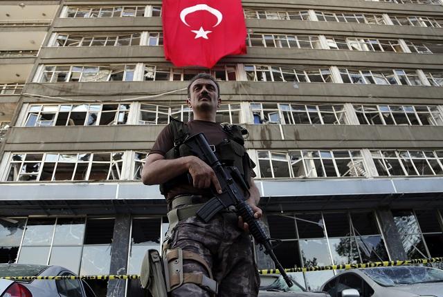 Príslušník špeciálnych síl tureckej polície stojí pred poškodenou budovou na policajnej základni v Ankare 19. júla 2016. Základňu napadli stíhacie lietadlá rebelov počas pokusu o prevrat